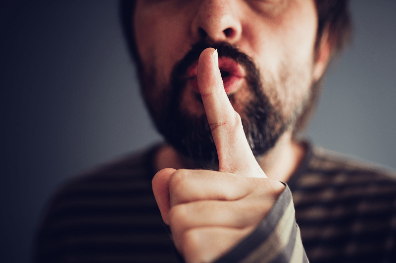 Man holding his finger to his lips to silence someone