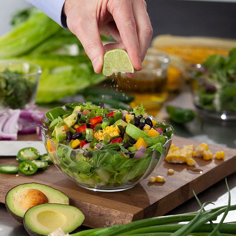 Person squeezing Lime onto healthy salad