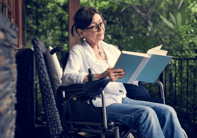 woman sitting a wheelchair reading a book