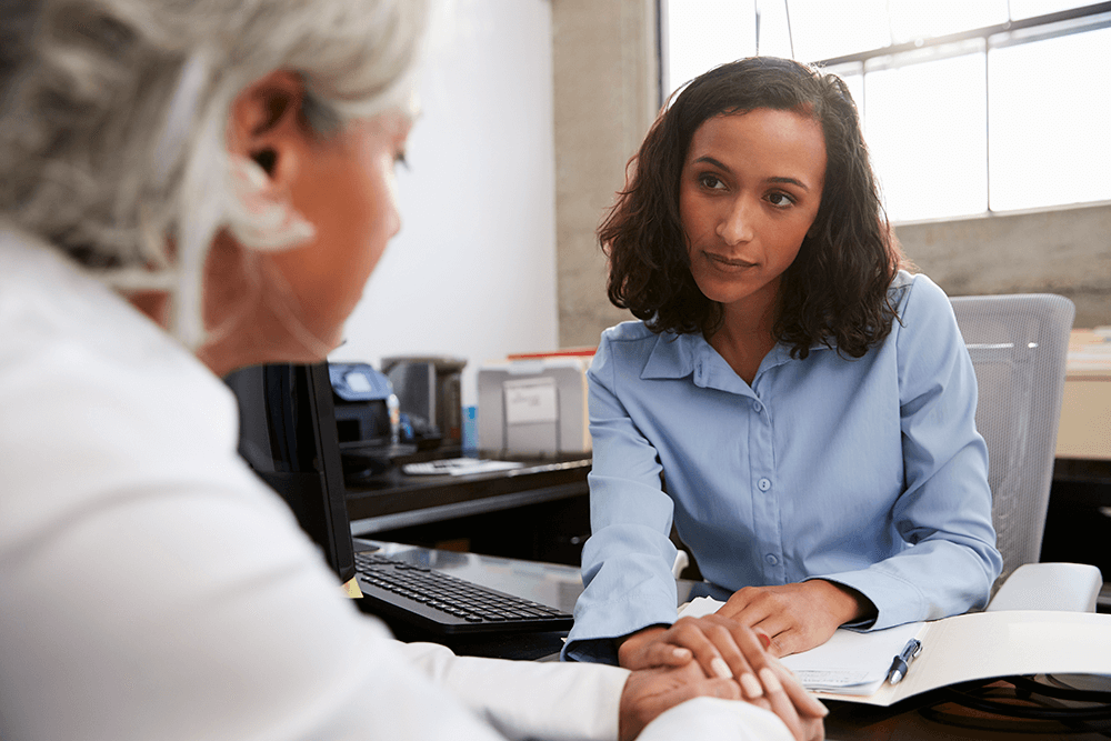 Concerned female doctor counselling senior woman