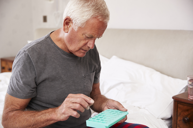 man sitting on bed at home taking medicine from organizer