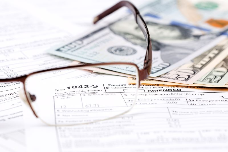 A pair of glasses sitting on a tax form
